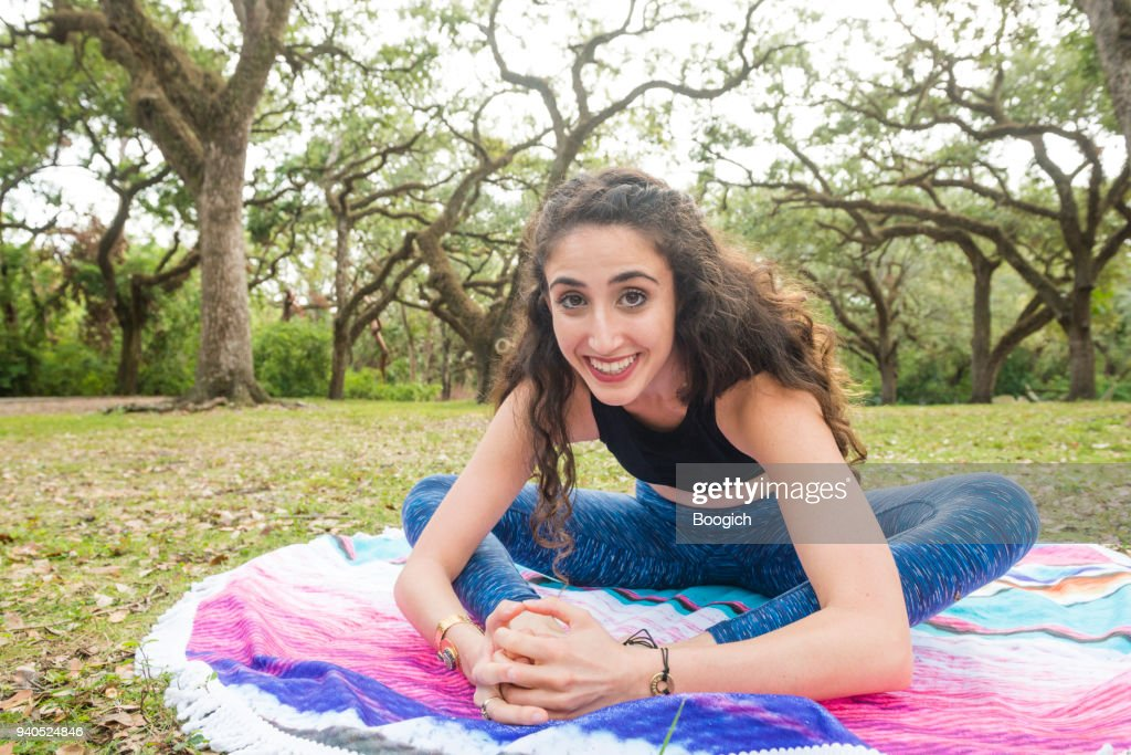 Smiling Millennial Woman In Baddha Konasana Yoga Pose Outdoors Miami Stock Photo