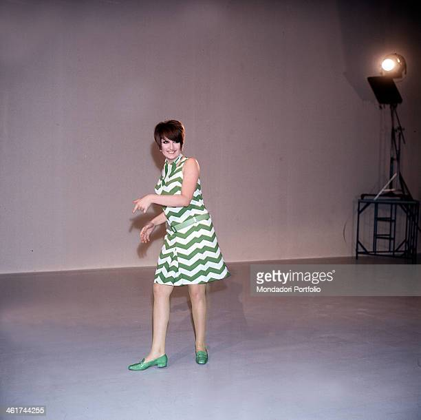 A smiling Mina born Mina Anna Maria Mazzini poses with a fashonable white and green dress into a TV studio the famous Italian singer is a permanent...