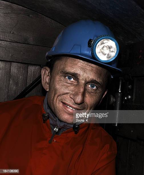 smiling miner with blue eyes wearing blue helmet with light - coal miner stock photos and pictures