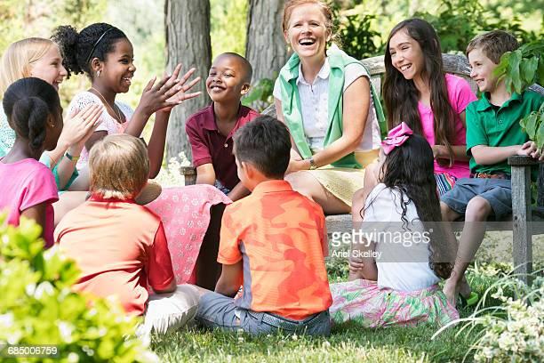 smiling minister mentoring children outdoors - multiculturalismo foto e immagini stock