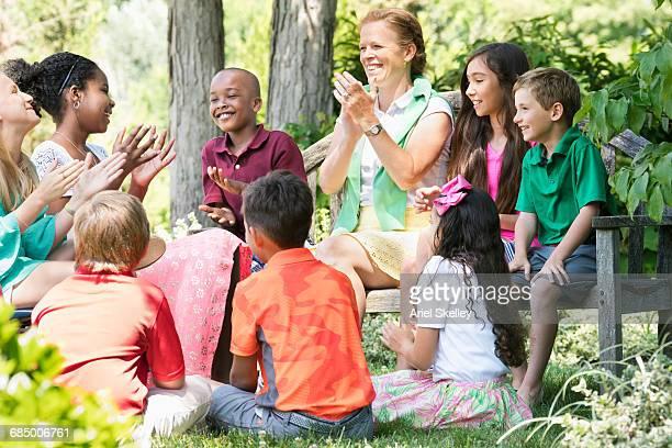 Smiling minister mentoring children outdoors