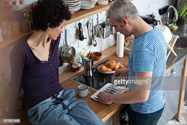 A smiling mixed age couple preparing food in their kitchen
