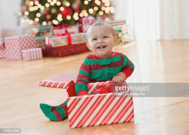 Smiling Mixed Race baby boy sitting on floor playing with Christmas box