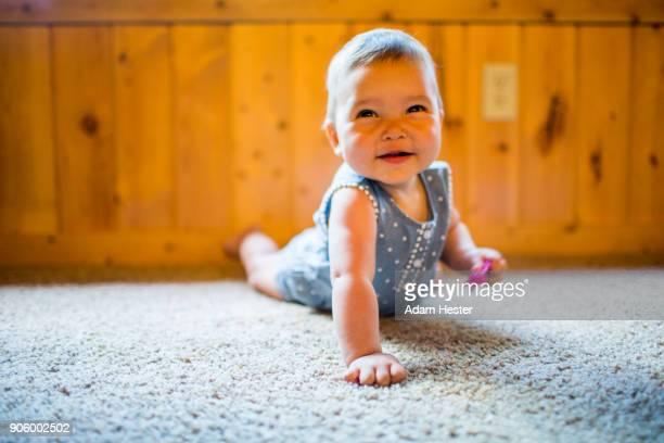 Smiling mixed race baby girl crawling on carpet