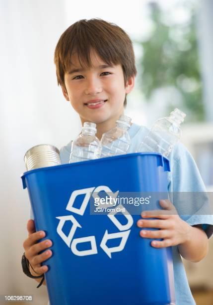 Smiling mixed race boy holding recycling bin