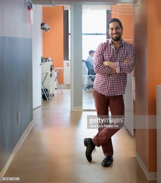 Smiling Mixed Race businessman leaning on office wall