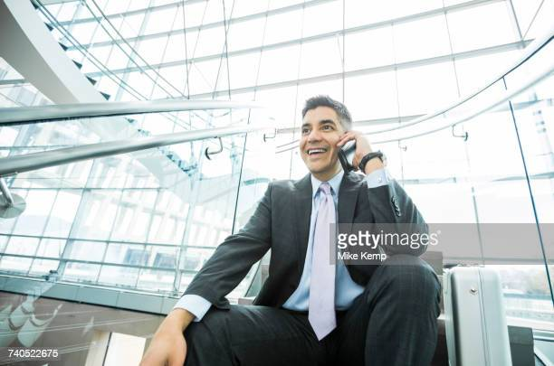 Smiling Mixed Race businessman sitting on staircase talking on cell phone