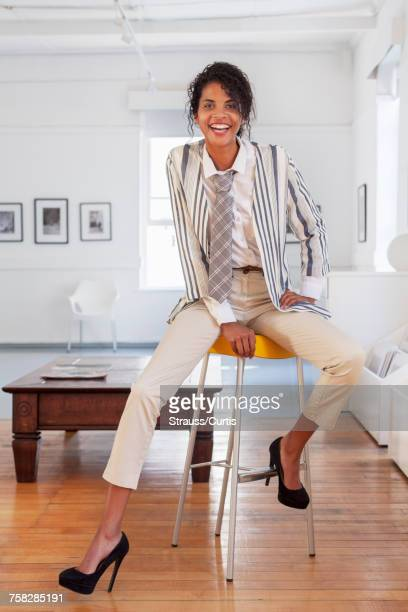 Smiling Mixed Race businesswoman sitting on stool