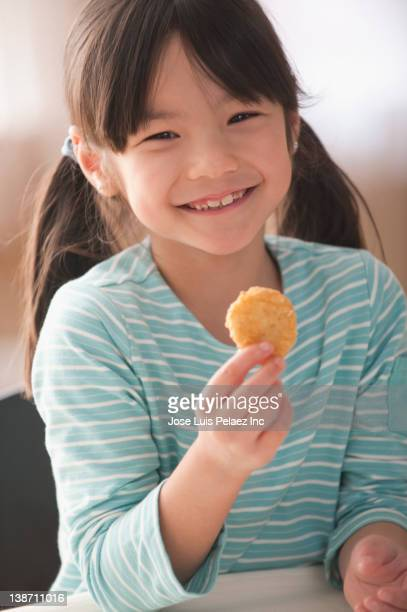 Smiling mixed race girl eating chicken nuggets