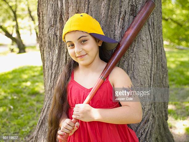 smiling mixed race girl holding baseball bat - baseball tattoo stock photos and pictures