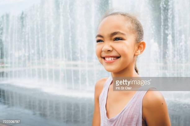 Smiling Mixed Race girl near fountain