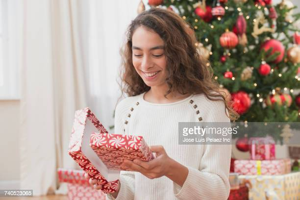 Smiling Mixed Race girl opening Christmas gift