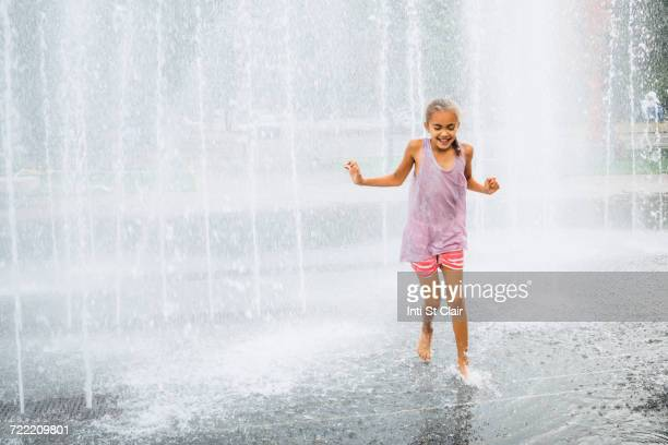 smiling mixed race girl running fountain - wet girl stock photos and pictures