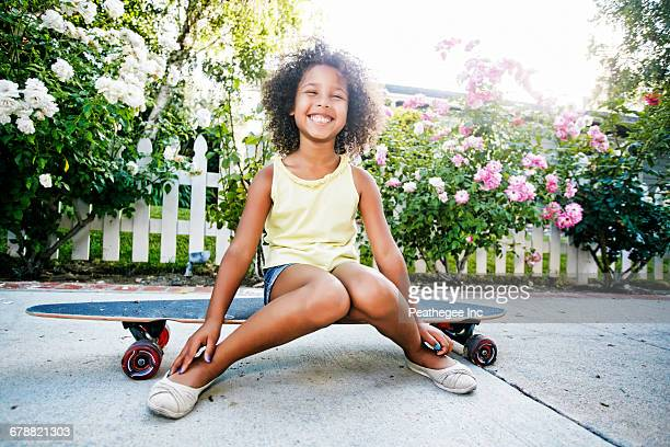 Smiling Mixed Race girl sitting on skateboard