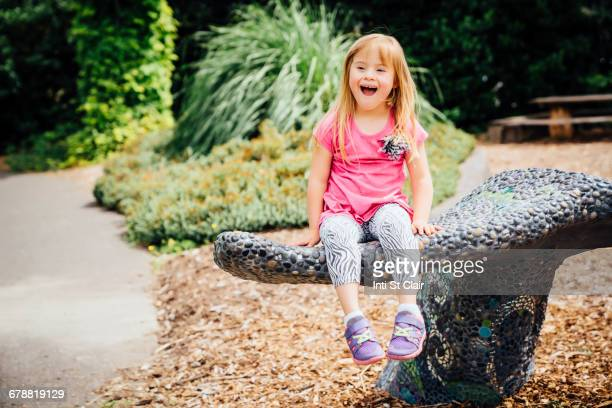 Smiling Mixed Race girl sitting on stone bench in park