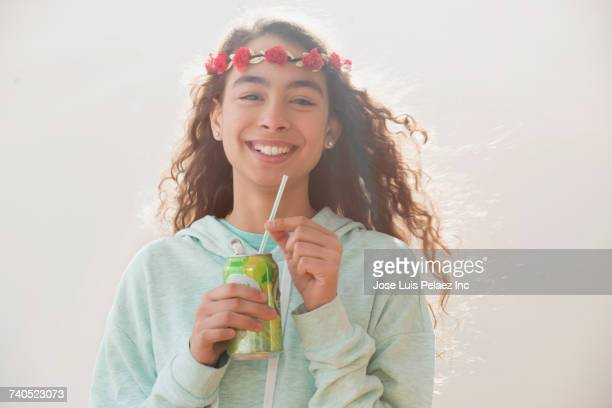 Smiling Mixed Race girl wearing flower headband drinking from can with straw