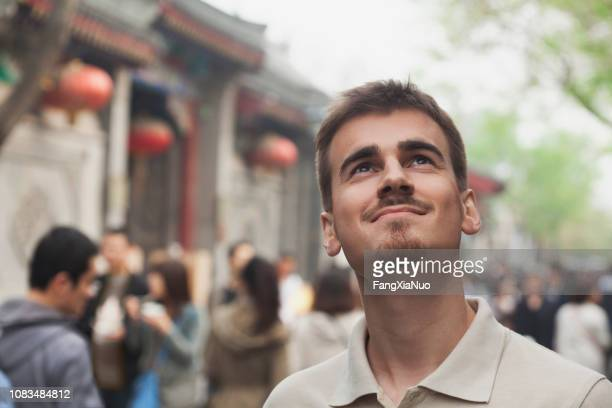 smiling mixed race man looking up outdoors - goatee stock pictures, royalty-free photos & images