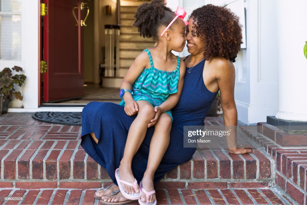 Smiling mixed race mother and daughter rubbing noses on front stoop : Stock Photo