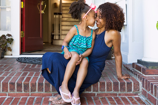 Smiling mixed race mother and daughter rubbing noses on front stoop - gettyimageskorea
