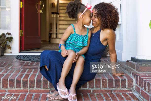 Smiling mixed race mother and daughter rubbing noses on front stoop