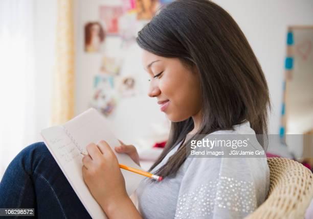 Smiling mixed race teenage girl writing in journal