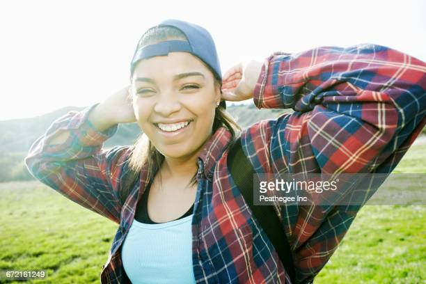 smiling mixed race woman backpacking in field - plaid shirt stock pictures, royalty-free photos & images