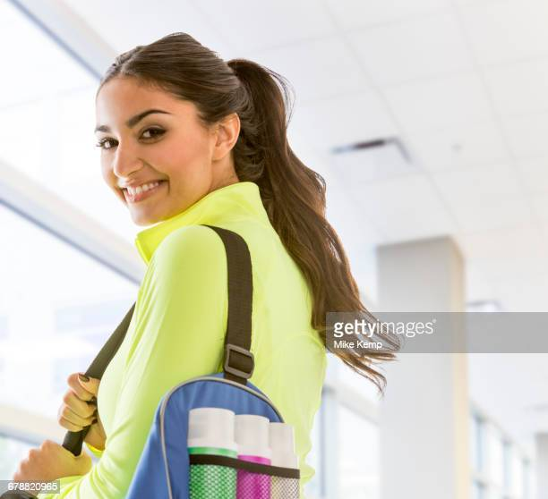 smiling mixed race woman carrying bag at gymnasium - gym bag stock pictures, royalty-free photos & images