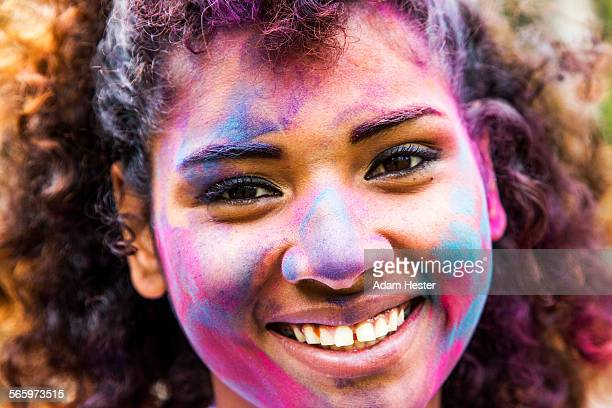 Smiling mixed race woman covered in pigment powder