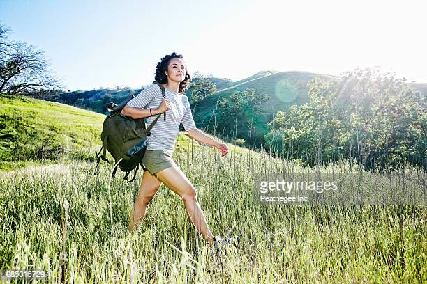 smiling mixed race woman hiking on hill - 膝から上の構図 ストックフォトと画像