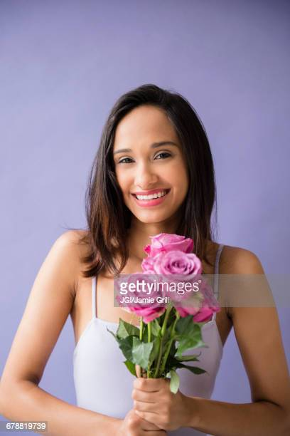 Smiling Mixed Race woman holding bouquet of roses