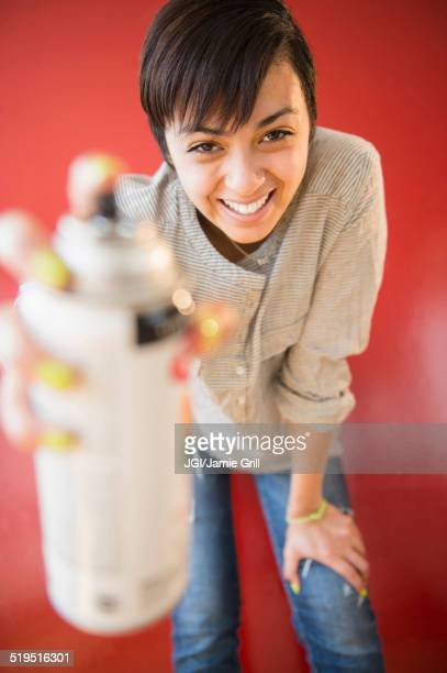 Smiling mixed race woman holding canister of spray paint