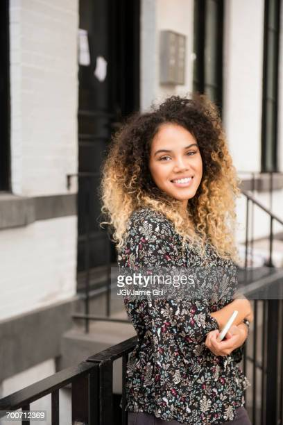 Smiling Mixed Race woman holding cell phone in city