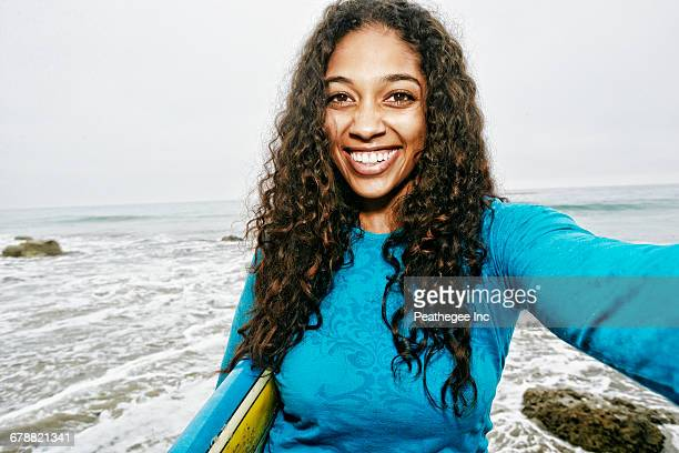 Smiling Mixed Race woman holding surfboard posing for selfie at beach