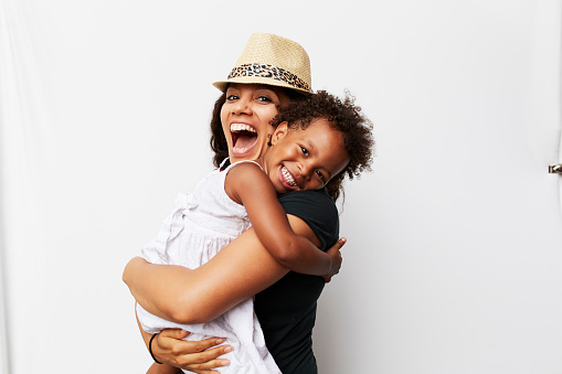 Smiling Mixed Race woman hugging daughter - gettyimageskorea