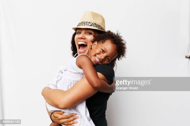 smiling mixed race woman hugging daughter - three quarter length stock pictures, royalty-free photos & images