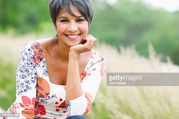 smiling mixed race woman in field - hand on chin stock pictures, royalty-free photos & images