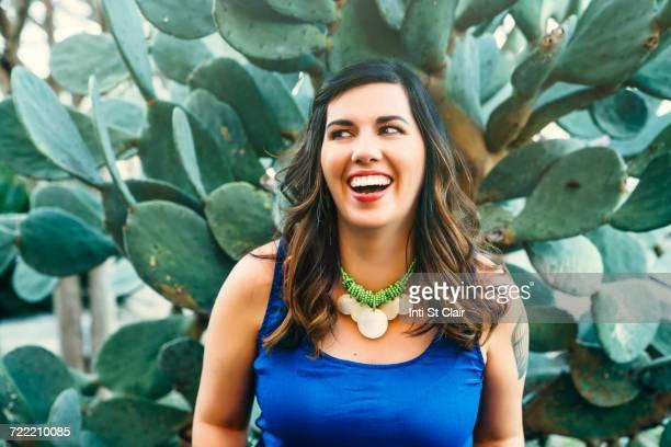 Smiling Mixed Race woman near cactus