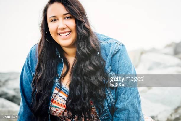 Smiling Mixed Race woman near ocean