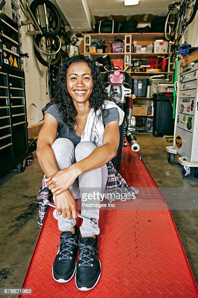 Smiling Mixed Race woman sitting on repair stand in garage
