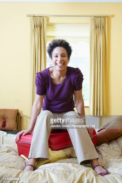 Smiling mixed race woman sitting on suitcase
