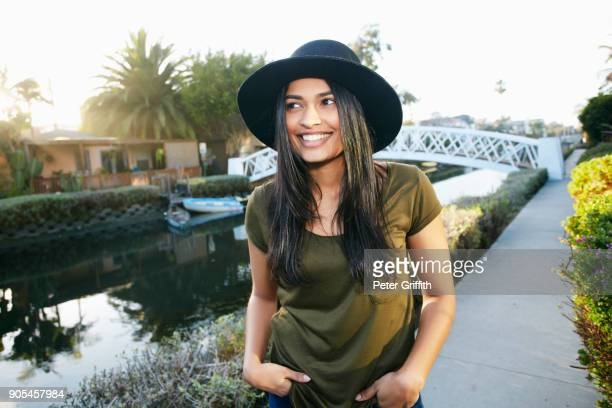 Smiling mixed race woman standing near canal