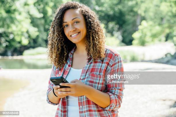 Smiling mixed race woman texting on cell phone outdoors