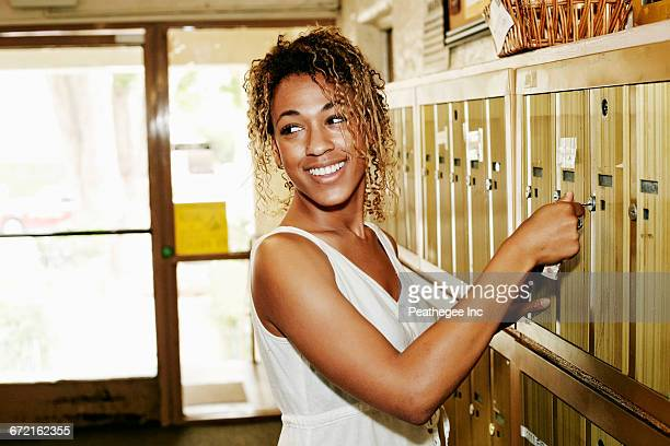 Smiling Mixed Race woman unlocking apartment mailbox
