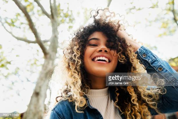smiling mixed race woman with hand in hair - curly stock pictures, royalty-free photos & images