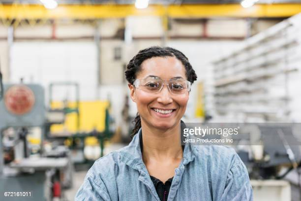 Smiling Mixed Race worker in factory
