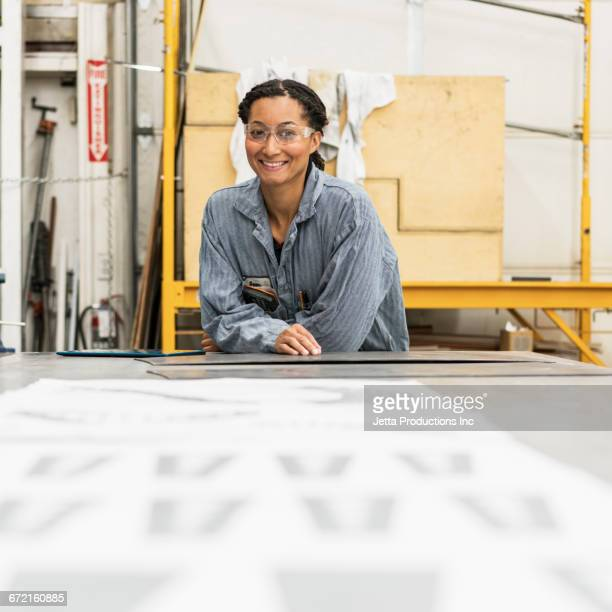 Smiling Mixed Race worker posing at table in factory