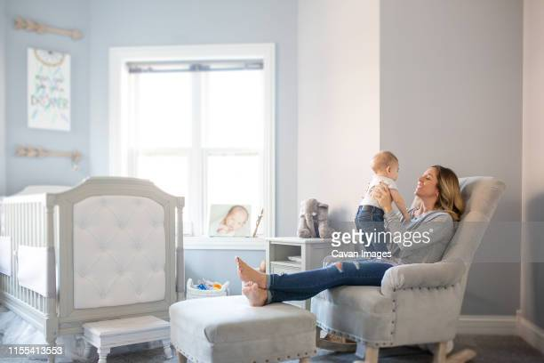 smiling mom holding baby boy in chair in nursery - nursery bedroom stock pictures, royalty-free photos & images