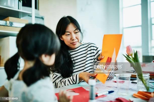 smiling mother admiring daughters handmade valentines day card - kunst und kunsthandwerk stock-fotos und bilder