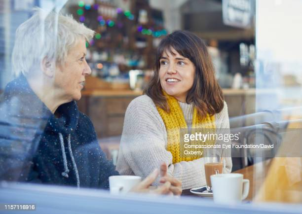 """smiling mother and adult daughter drinking coffee and talking in cafe - """"compassionate eye"""" stock pictures, royalty-free photos & images"""