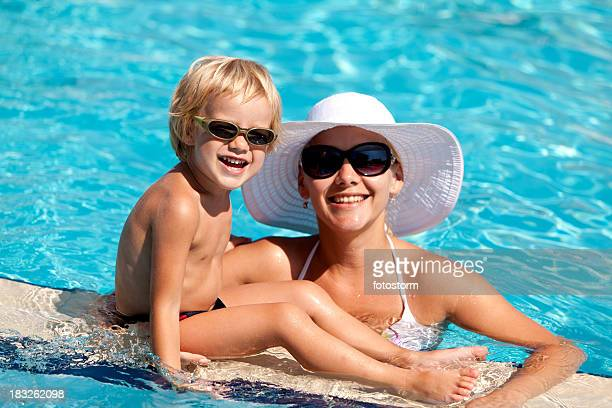 Smiling mother and child with sunglasses in the swimming pool